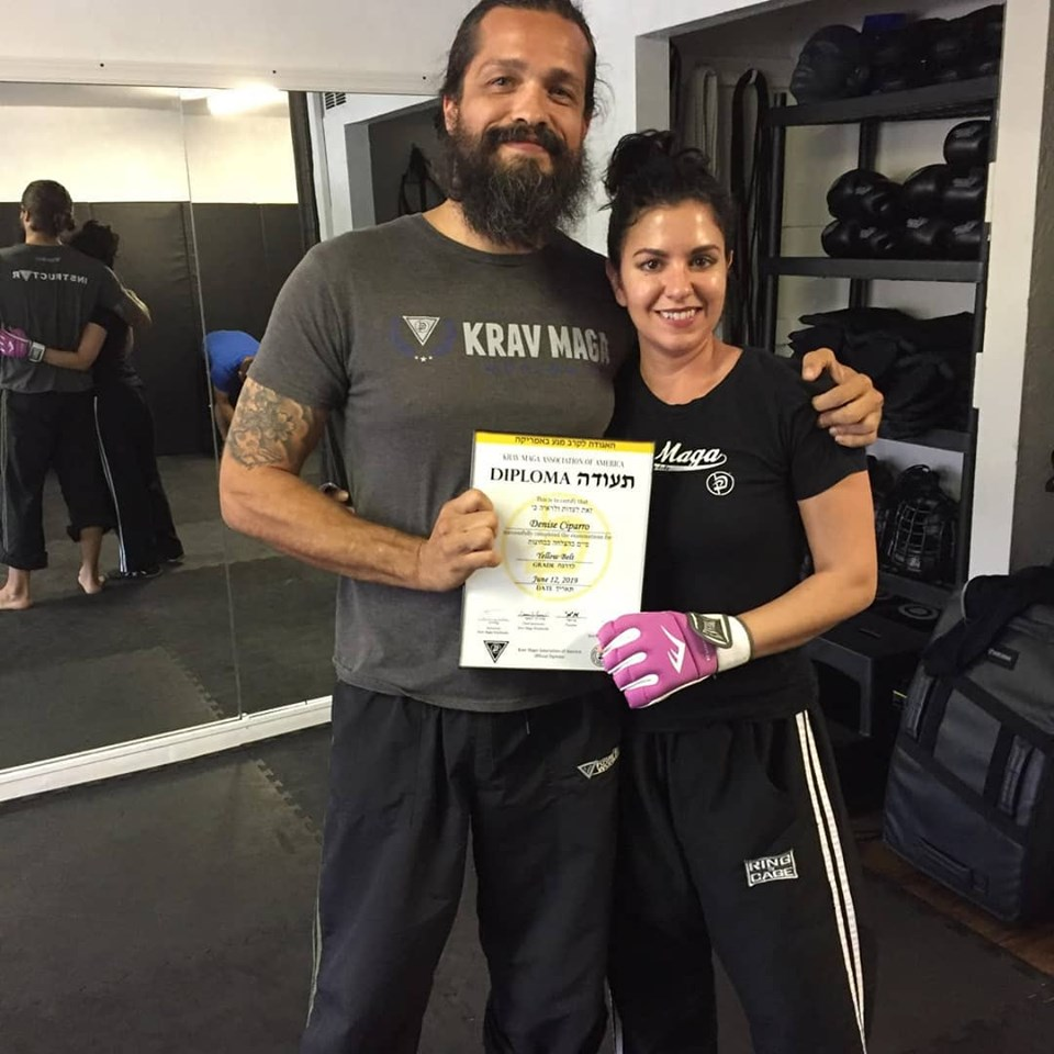 Denise Ciparro receiving her Krav Maga yellow belt diploma.