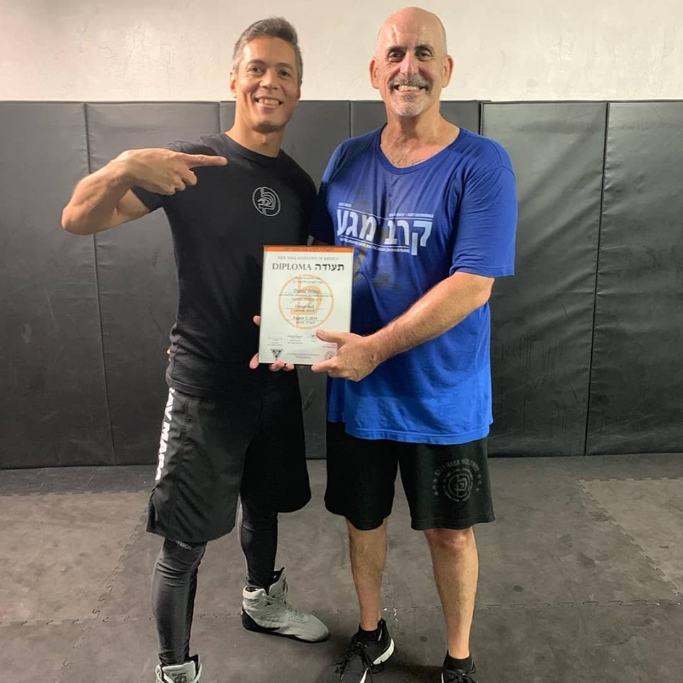 David Weiss receiving his Krav Maga orange belt diploma