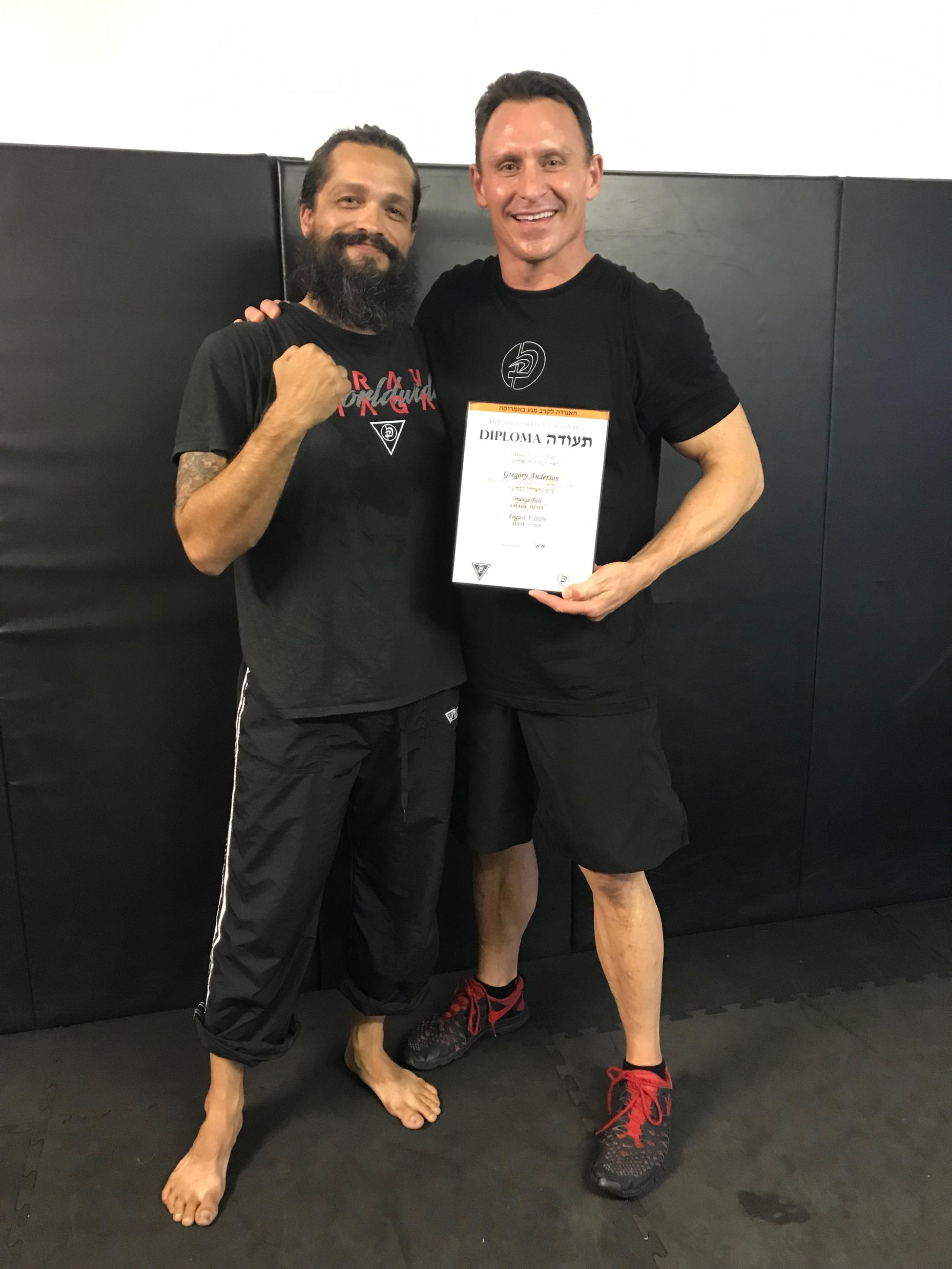Greg Anderson receives his Krav Maga orange belt diploma