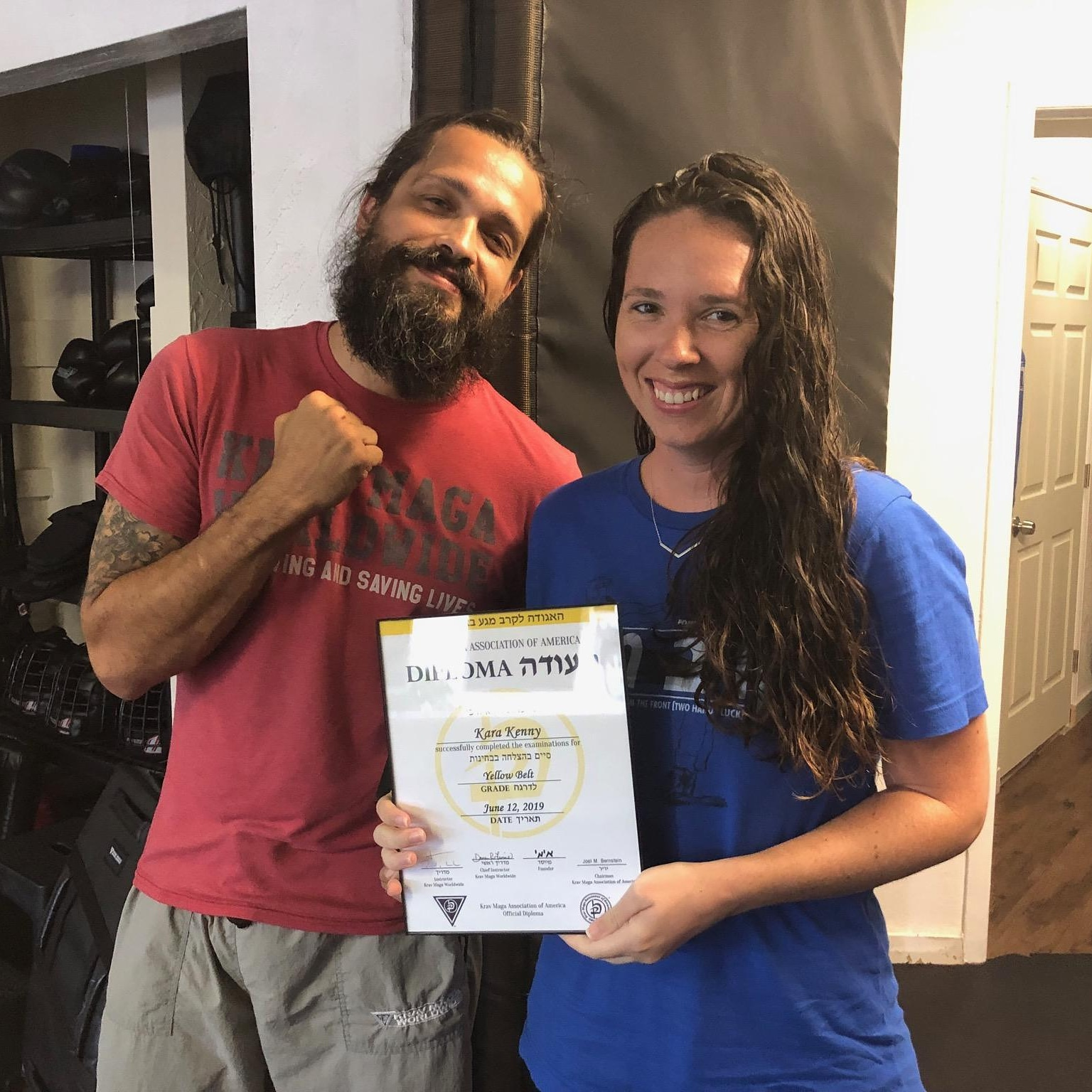 Kara Kenny receives her Krav Maga yellow belt diploma.