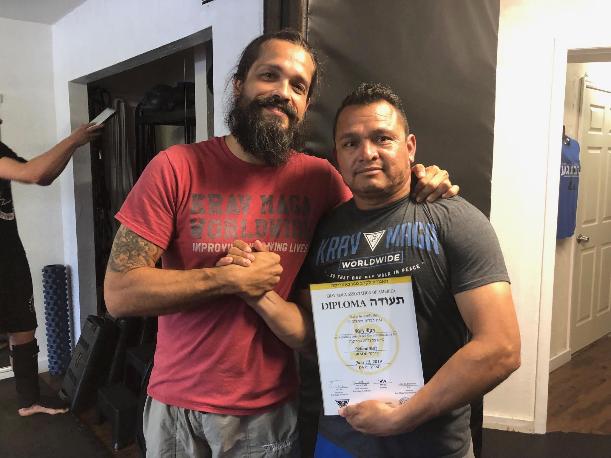 Ray Romero receiving his Krav Maga yellow belt diploma.