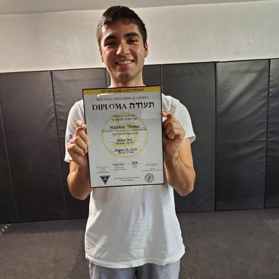 Matthew Thomas receiving his Krav Maga yellow belt diploma