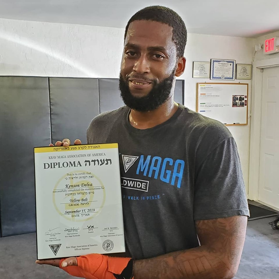 Kenson Delva receving his Krav Maga yellow belt diploma