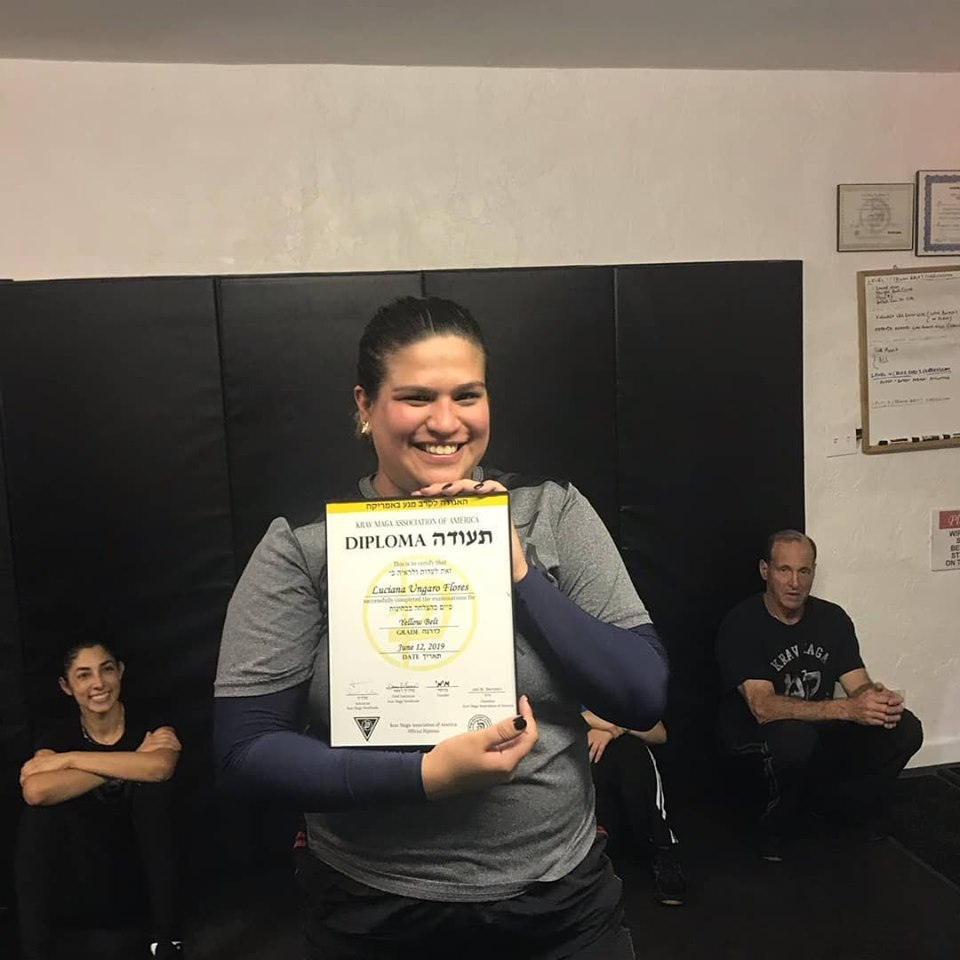Luciana Ungaro Flores receiving her Krav Maga Yellow Belt diploma